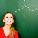 Woman standing in front of blackboard with thought bubbles drawn on it
