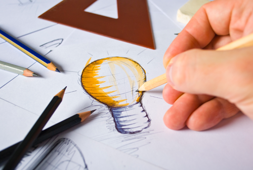 Person drawing a lightbulb logo