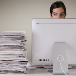 Man sitting at his computer with a pile of documents next to him